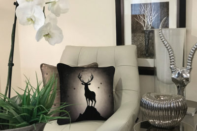 Hecuba I Decorative Stag Cushion on Luxury Chair in Lounge.